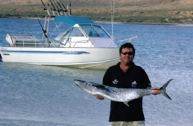 Mackeral, Spanish - Dwayne Crofts with a great Spanish Mackeral pictured here in front of the purpose designed 21ft Star Aluminium offshore boat at Exmouth, Western Australia.
